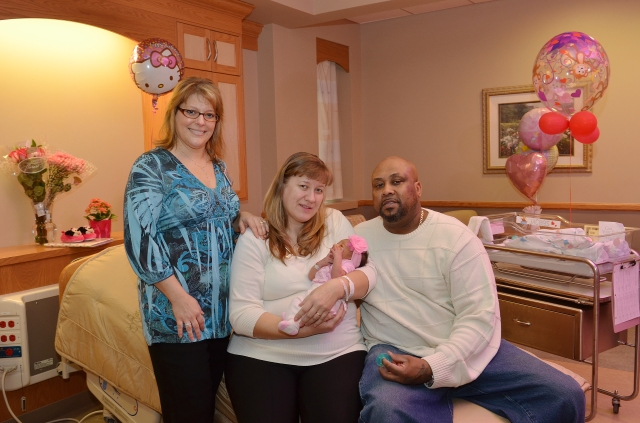 Certified nurse midwife Heather Shannon with new parents, and James Jacobs and their daughter.