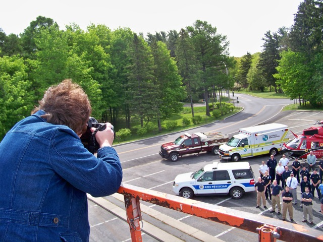 Photographer Susan Kahn takes a group photograph of emergency responders and physicians in the parking lot at Upstate University Hospital's Community Campus