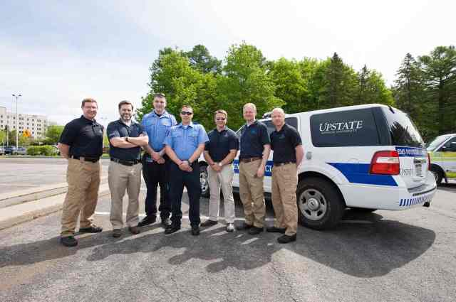 Upstate paramedic students Derek Natoli and Jordan Shultz, center, are surrounded by Upstate EMS & Disaster Medicine physicians Derek Cooney, Christian Knutsen, David Landsberg, Charles Beaudette and Jeremy Joslin.