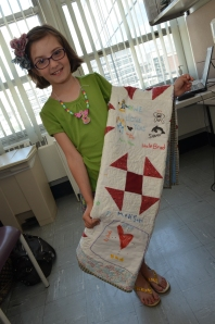 Madison Green shows the quilt she received from the Towpath Quilt Guild.