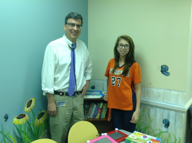 Girl Scout Nicole Abbott stands with her doctor, Dr. William Hannan, MD in front of the bookshelf she donated.