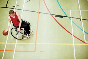 wheelchair bound man bounces basketball. Shot from above.