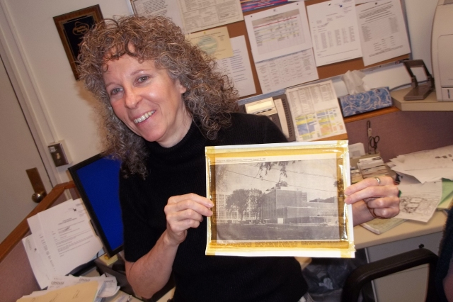 Mary Lent holds a 50-year-old news clipping showing construction of the hospital at Upstate's downtown Syracuse campus.