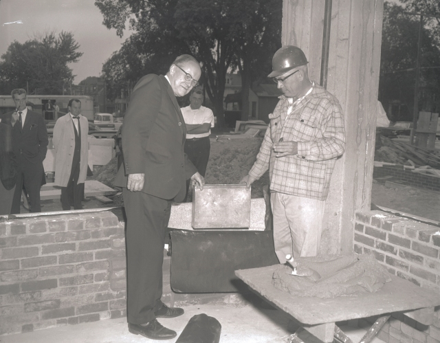Upstate President Carlyle Jacobsen, PhD (1902-1974) and an unidentified man place a time capsule in the cornerstone of Upstate's downtown campus hospital, 1963.