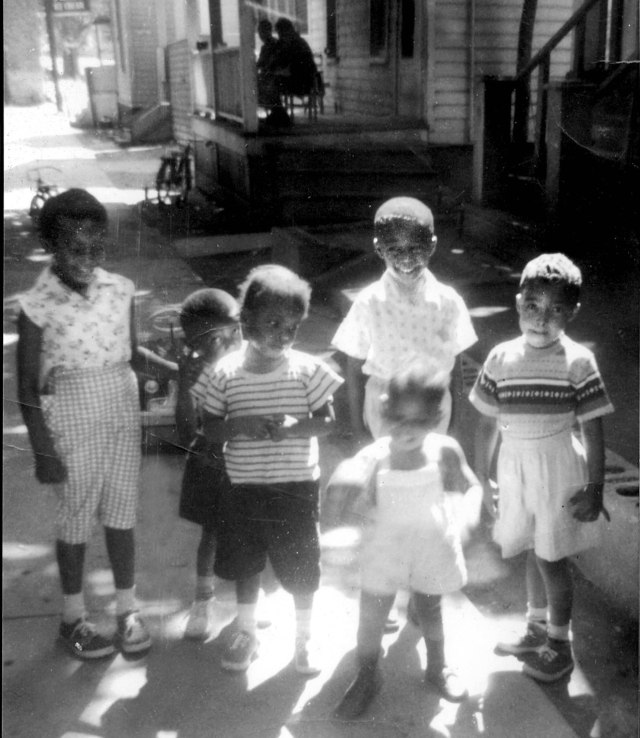 Samuel Roberts (on the right in a striped sweater) with friends and relatives at his childhood home on Rose Ave. — a one block street, down the hill from what would be Upstate University Hospital.  Circa 1960.