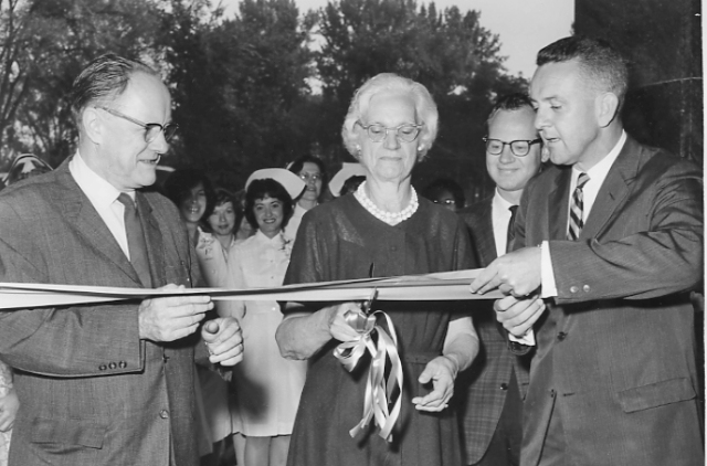 "Estella Nolta, the first patient at Upstate University Hospital, downtown, cuts the ribbon on July 20, 1964. She is flanked by Upstate President Carlyle ""Jake"" Jacobsen PhD on the left and James Abbott, vice president for hospital affairs, on the right."