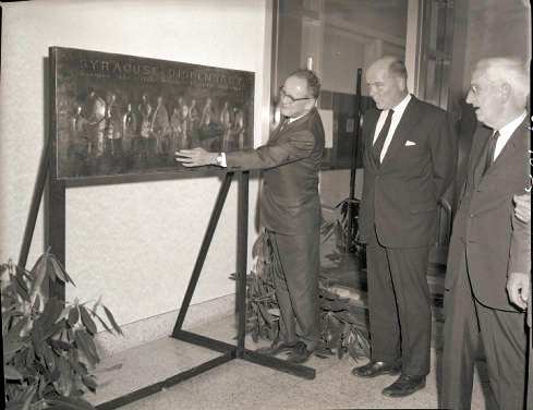 "July 1964: Upstate President Carlyle ""Jake"" Jacobsen, PhD, discusses the commemorative bronze plaque with colleagues."