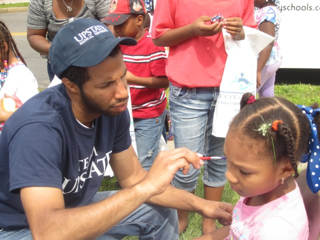 Medical student Alex Rodriguez paints the face of a young student at the Back To School Barbeque.