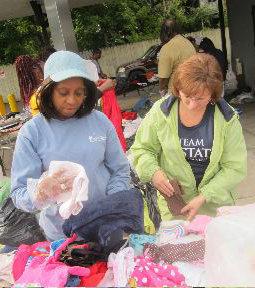 Upstate employees Joyce Freeman and Colleen McManus sort donated clothes to give away at the barbeque.