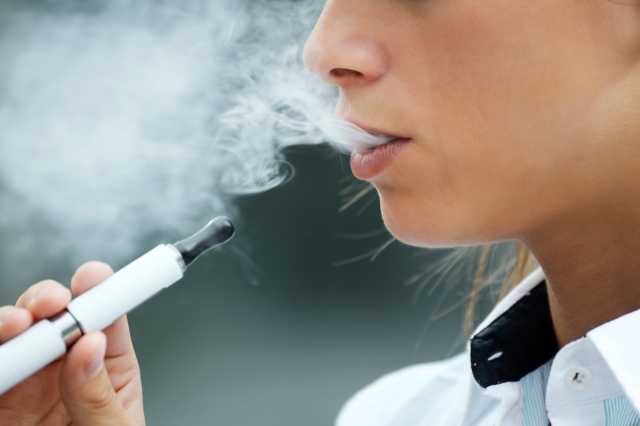 closeup of woman smoking electronic cigarette outdoor