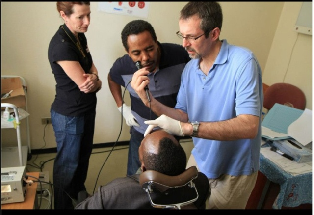 Using a flexible scope, Rick Kelley, MD, examines a patient's nasopharynx and voice box with Muluken Bekelle, MD, the first ear, nose and throat doctor Kelley trained in Ethiopia, equipping him with clinical and operating room instruments.