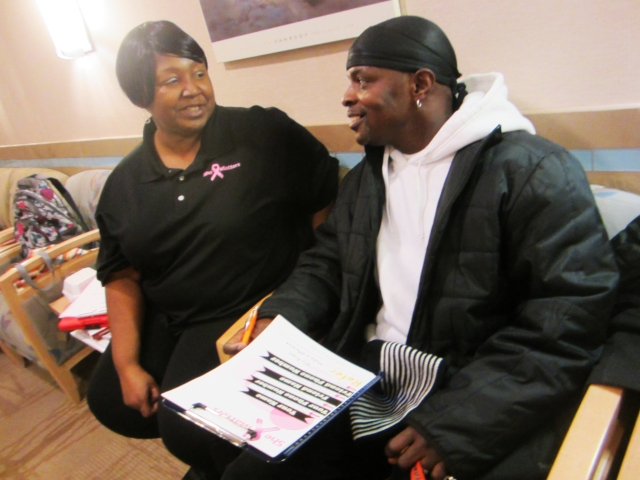 "She Matters advocate Martha Chavis-Bonner helps her neighbor, Edward Moody, sign his wife up for a mammogram at the Patricia J. Numann Center for Breast, Endocrine and Plastic Surgery at the Upstate Specialty Services Center. Moody's wife, says Chavis-Bonner, is typical of many African American women: ""so busy working and taking care of her family that she doesn't take time for her own health."""