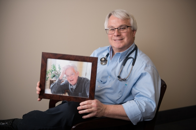 Timothy Creamer, MD, holds a photo of his father, George. Creamer is division chief of hospital medicine at Upstate University Hospital, Community Campus. PHOTO BY SUSAN KAHN.