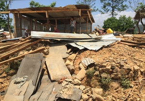 A family assesses the damage to their home in Sindhupalchowk, a district hit hard by the Nepal earthquake.(PHOTO COURTESY OF DINESH SUBEDI, MD)