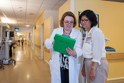 Brain injury medicine specialist Bernadette Dunn, MD, discusses a patient's progress with nurse manager Virginia Castro.