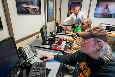 Joe Huber (background, standing) works with (from front to back) Robert Chapman, Jorge Varona and Patrick Carroll in the computer lab at the Rescue Mission on GIfford Street in Syracuse. (PHOTO BY ROBERT MESCAVAGE)