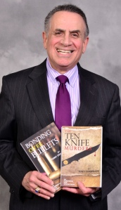 Tony Cerminaro, NP, with two of the murder mysteries he has written.