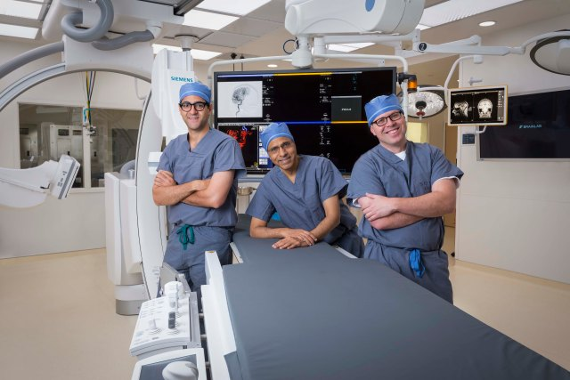 Hesham Masoud, MBBCh, Amar Swarnkar, MD and Grahame Gould, MD, in the bi-plane angiography operating room at Upstate University Hospital. Its location, in the new intraoperative MRI surgical suite, enables surgeons to obtain MRI scans during surgeries, improving patient outcomes.