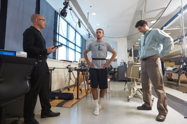 Slack, center, stands on a straight line with his eyes closed to test his physical functions, watched by athletic trainer Joshua Baracks (left) and project director Christopher Neville, PhD. Before that, test subjects are asked to recite a series of words and count backwards, and afterward, an EEG is used to track and record brain patterns.