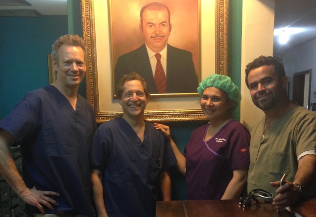Syracuse ophthalmologists Thomas Bersani, MD, and Robert Wiesenthal, MD, with their Honduran colleagues Drs. Alicia Ponce and Luis Sanilo in from of a portrait of the clinic's founder, Luis Alberto Ponce.