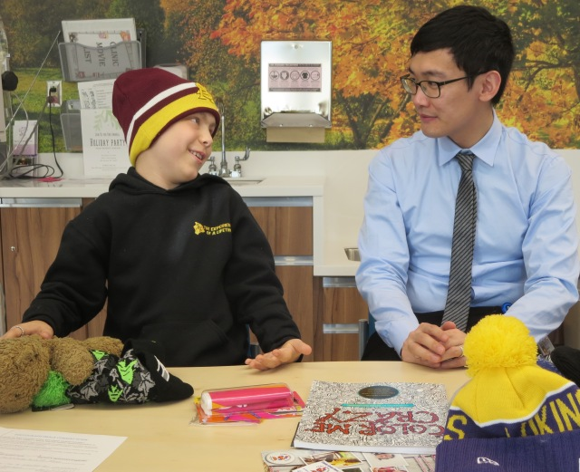 Medical student Shunqing Zhang lets cancer patient Connor Stanton, 10, choose from a collection of New Era hats. The youngster (son of Rebecca Quilty of Whitney Point) was especially pleased to find one for his favorite NFL team, the Seattle Seahawks. (PHOTO BY JIM McKEEVER)