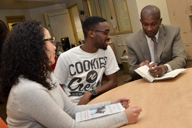 "New York Times bestselling author Damon Tweedy, MD, (right) signs a copy of his book, ""Black Man in a White Coat,"" for medical student Adekorewale Odulate-Williams, MS II, as Angela Rios, MSI, looks on. Tweedy, assistant professor of psychiatry and behavioral sciences at Duke University School of Medicine, gave two lectures and did a book signing with current and incoming students at Upstate on Feb. 10 in honor of Black History month. Photo by Debbie Rexine."