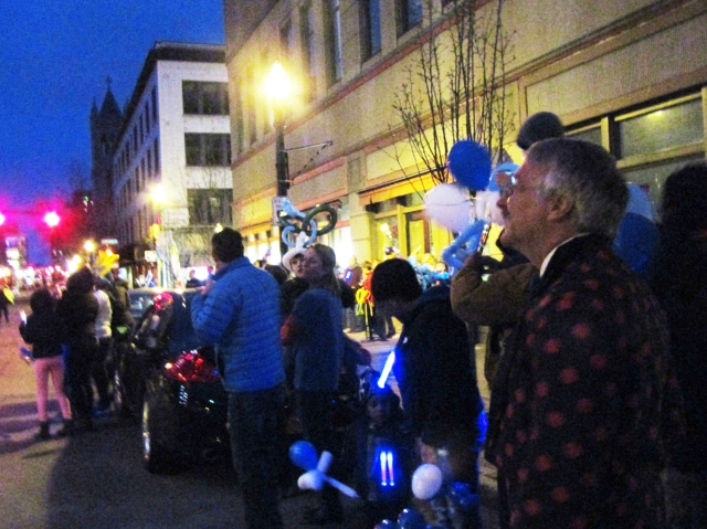 The crowd gathers as Jefferson Tower — and the night sky — light up blue in recognition of autism