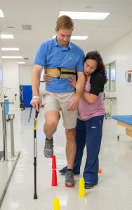 Physical therapist Daisy Sandbek works with Reger in University Hospital's Rehabilitation Center last September. (PHOTO BY ROBERT MESCAVAGE)