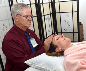Bob Crandall provides Reiki for Bailey Colvin, a patient at the Upstate Cancer Center. (PHOTOS BY DEBORAH REXINE)