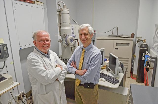 Donald Balir, MD, and Jerrold Abraham, MD, in their Upstate lab with the microscope they used to isolate the NY_v014 poxvirus. (PHOTO BY DEBORAH REXINE)