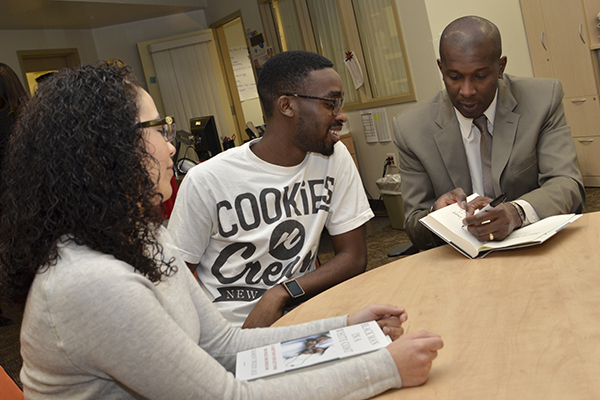 Author Damon Tweedy, MD, signs a copy of his book, Black Man in a White Coat, for Upstate medical student Adekorewale Odulate-Williams as Angela Rios, another Upstate medical student, looks on.