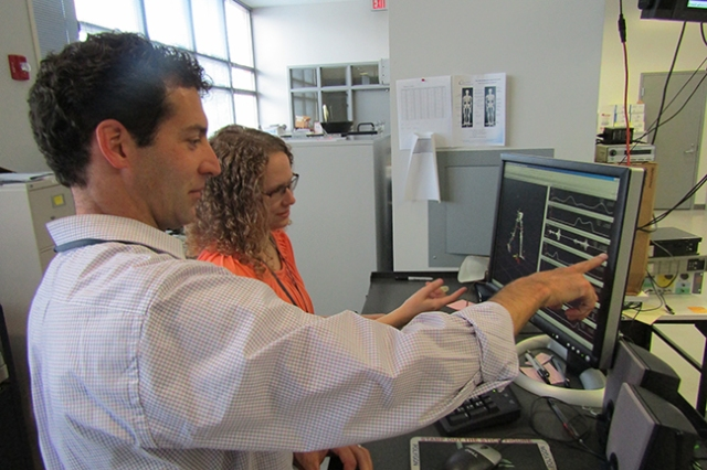 Christopher Neville, PT, PhD, and research assistant Julia Rogers in the Motion Analysis Lab at Upstate. They are reviewing files associated with Neville's studies on the mechanical effects of flatfoot deformity. Photo by Susan Keeter