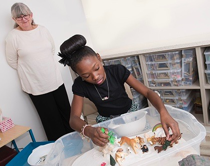 Knai Bridges, 13, creates a sandplay assemblage as Ruth McKay, medical family therapist looks on. (PHOTOS BY SUSAN KAHN)