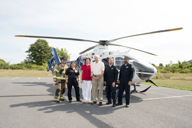 Larry Deshaw and his wife, Nancy Humphrey (center) reunited with rescuers in Clayton about a month after he suffered a stroke. This is the parking lot of the Clayton Fire Department, where the LifeNet helicopter picked Deshaw up to transport him to the comprehensive stroke center at Upstate.