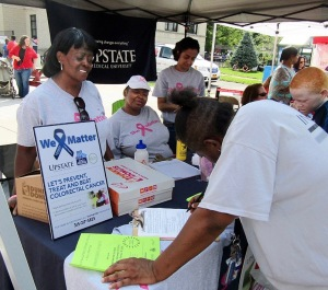 Janet Bacon (left) and Martha Chavis-Bonner (seated), both of whom are resident health advocates, sign people up for mammograms and colorectal cancer screening at the Mary Nelson Back to School Barbecue, held in August in Syracuse. (PHOTO BY SUSAN KEETER)