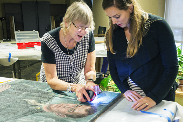 Art conservator Susan Blakney uses an LED light to examine the World War II portrait of Arthur Ecker, MD, PhD, founder of the neurosurgery department at Upstate Medical University. Cara Howe, Upstate's curator of historical collections, observes. (PHOTO BY WILLIAM MUELLER)