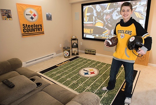 "Parker Hysick in his Pittsburgh Steelers-themed ""man cave,"" a gift from Make a Wish Central New York. (PHOTOS BY SUSAN KAHN)"
