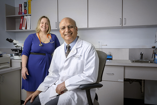 Kazim Chohan, PhD (seated), leads Upstate's Male Fertility Preservation Program, which came about through the efforts of Chohan and colleagues including pediatric oncologist Jody Sima, MD (standing); (and, not pictured) urologist JC Trussell, MD; oncologist Rahul Seth, DO; and pathology chair Robert Corona Jr., DO. (PHOTO BY ROBERT MESCAVAGE)