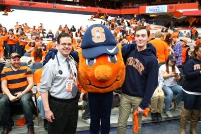 Upstate emergency physician Christopher Tanski poses with Otto the Orange and SU student Alex McMillan, who was revived when his heart stopped during the basketball game on Feb. 4. Photo by Mike Okoniewski/Syracuse Athletics