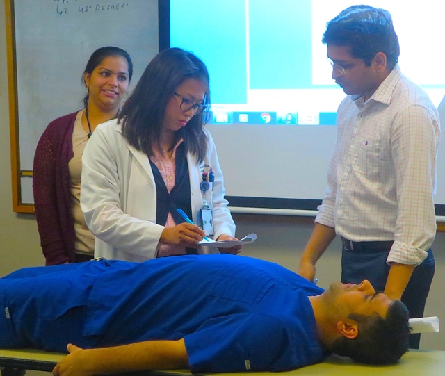 """Chief neurology residents Gurmeen Kaur, MBBS (left), and Vishal Shah, MBBS (right), facilitate a stroke simulation with resident Claribel Wee, MD, and a """"patient"""" (Puneet Kapur, MD)."""