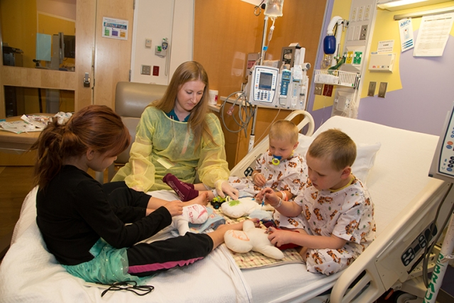 Maggie Zick, a certified child life specialist at Upstate Golisano Children's Hospital, leads the Delaney brothers, Trevor and Michel, and their sister Elizabeth in medical play at the bedside. Medical play is a tool that child life specialists use to explain procedures to patients and that offers a way to include siblings, who may feel left out. This photo was selected for the 2017-2018 Children's Hospital Association's traveling photo exhibition, which promotes the value of children's hospitals nationwide. (PHOTO BY KATHLEEN PAICE FROIO)
