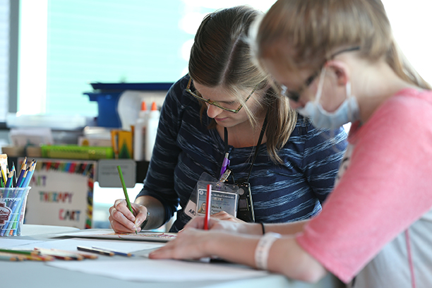 Alexis works on an art project with Fazzini. Upstate Golisano Children's Hospital also holds exhibitions of art created by patients.