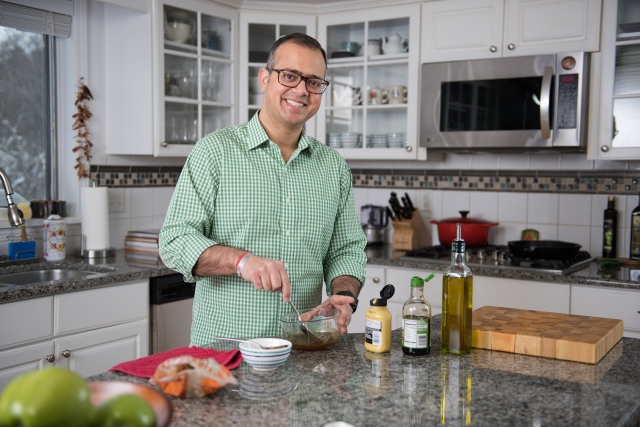Prateek Wali, MD, in his kitchen preparing a marinade for salmon (see recipe below). (PHOTO BY SUSAN KAHN)