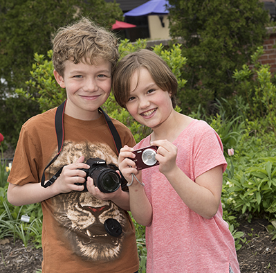 Ashton and Jordan Miller at the Rosamond Gifford Zoo at Burnet Park in Syracuse. They like to photograph animals and have raised money for the zoo's Adopt an Animal program. (PHOTO BY SUSAN KAHN)