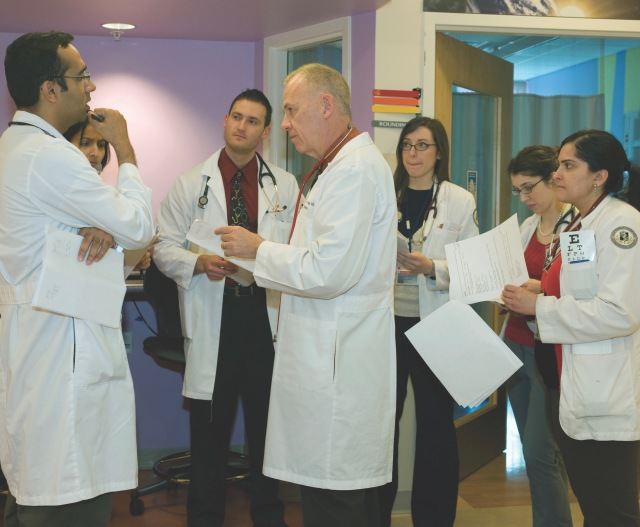 Thomas Welch, MD (center), with a group of medical residents and students at the Upstate Golisano Children's Hospital. (PHOTO BY SUSAN KAHN)