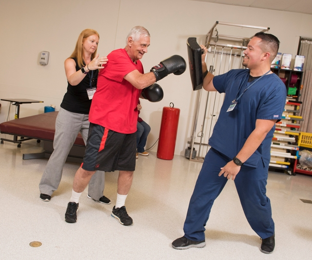 Physical therapist Kelly Grier, left, tailored a recovery program for William Bouchard, an avid martial artist, that included boxing. Physical medicine and rehabilitation student Joey Feliciano assisted by holding targets for Bouchard. (PHOTO BY SUSAN KAHN)