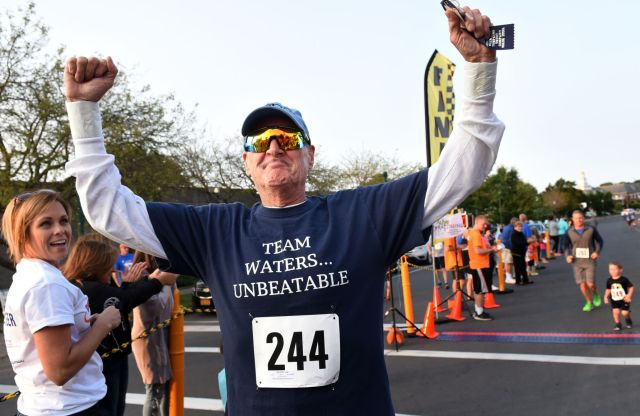 Jim Waters, who has stage IV colon cancer, raises his arms in victory after finishing the Downtown Auburn Mile in August. (PHOTO BY KEVIN RIVOLI/THE AUBURN CITIZEN/AUBURNPUB.COM)