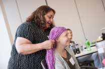 Cosmetologist Angela McBride shows a group of teenagers with cancer how to wrap scarves into turbans, with help from Taylor Way, 15. (PHOTO BY SUSAN KAHN)