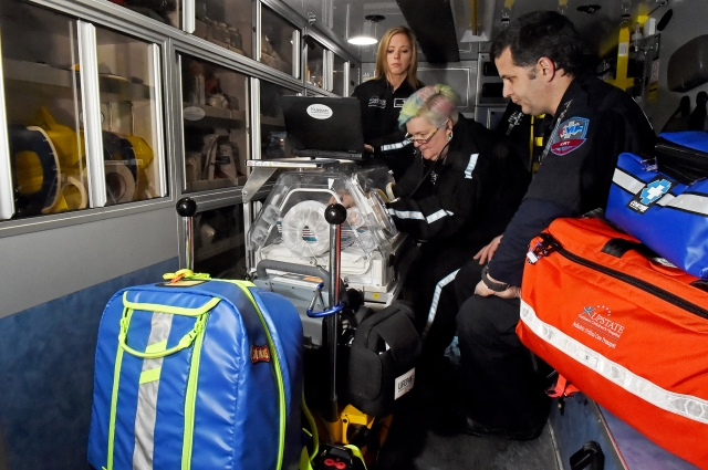 Nurses Arlinda Carey and Melanie Charleston prep an incubator in the back of an ambulance at Upstate University Hospital's downtown emergency department.  They are members of Upstate's pediatric critical care transport team who offer intensive care to critically ill children at other hospitals from the Canadian to the Pennsylvania borders. They are pictured with emergency medical technician Marc Battaglia, right. (PHOTO BY JOHN BERRY)