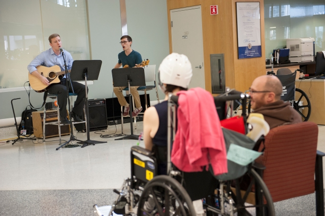 Medical students Benjamin Meath and Joe DeRaddo perform in the Upstate University Hospital lobby as Abigail and Stephen McSweeney listen. (PHOTO BY SUSAN KAHN)